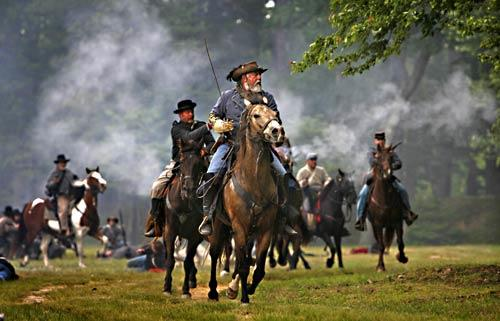 A Confederate commander leads his troops during a 2008 reenactment of a Civil War battle at Ft. Pocahontas in Charles City County, Va. On May 21 and 22, the battle will unfold again on the very ground where the original soldiers fought in 1864.