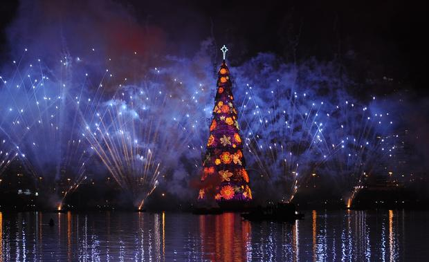 "Fireworks light up the sky during the inauguration of the floating Christmas ""tree"" in Rio de Janeiro's Rodrigo de Freitas lagoon. The 279-foot tall metallic structure, dubbed the world's tallest floating Christmas tree by the Guinness Book of Records, is lit by over three million lights and weighs 542 tons."