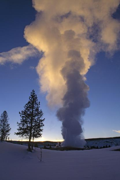 Old Faithful is seen erupting during winter.