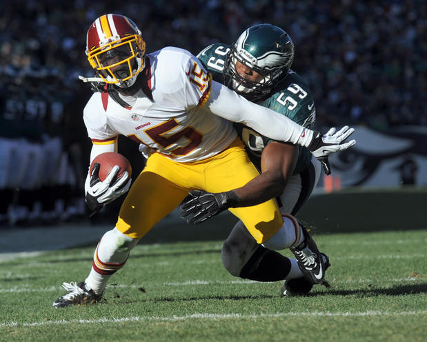 Washington Redskins wide receiver Josh Morgan (15) scores a touchdown as he is tackled by Philadelphia Eagles middle linebacker DeMeco Ryans (59)  at Lincoln Financial Field in Philadelphia on Sunday.