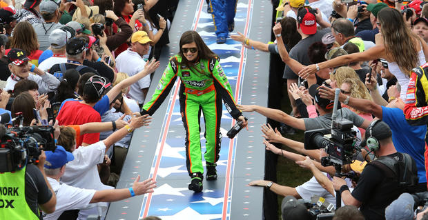 Danica Patrick low-fives fans during player introductions before the start of the Daytona 500 at Daytona International Speedway, Sunday, February 24, 2013.