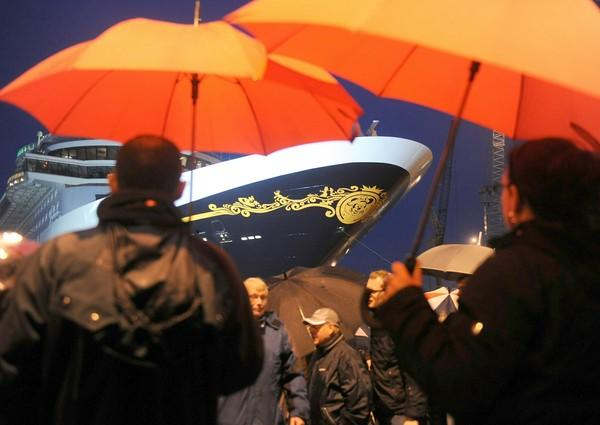 "Spectators shelters from the rain under umbrellas as they watch the launch of the new Disney Cruise Line ship, the ""Disney Dream"" at the Meyer Werft shipyards in the northern German city of Papenburg. The passenger ship is the largest to be built in Germany to date."