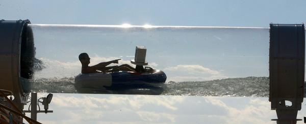 A rider points to an onboard camera, mounted to his raft, while riding the AquaDuck water coaster on the official christening cruise of the Disney Dream, from Port Canaveral, Fla., headed to the Bahamas, Wednesday, Jan. 19, 2011.