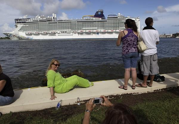 Carol Cox of Miami, left, poses for a photograph as the Norwegian Epic cruise ship arrives at the Port of Miami in Miami Wednesday, July 7, 2010. The new Norwegian Cruise Line megaliner will call the Port of Miami home.