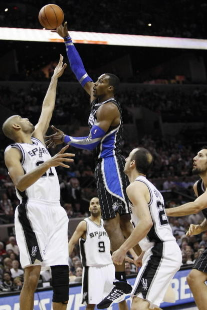 Orlando Magic center Dwight Howard (12) takes a shot over San Antonio Spurs forward Tim Duncan.