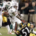 Miami running back Ricky Williams is tackled by Pittsburgh linebacker James Farrior