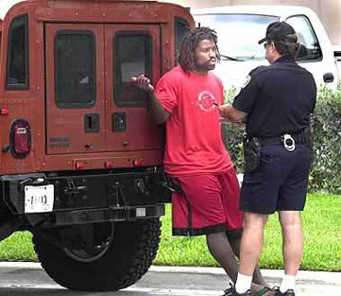 Dolphins running back Ricky Williams talks with a Fort Lauderdale Police officer after he was stopped while driving his burnt orange Humvee in the city's downtown shortly after his arrival in South Florida. Williams was issued three traffic citations and released after a police K-9 dog searched his vehicle.