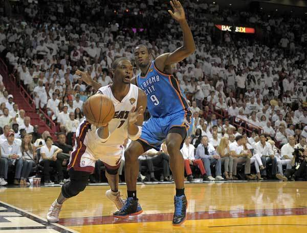 Miami Heat forward Chris Bosh gets rid of the ball after being fouled by Oklahoma City Thunder forward Serge Ibaka during the second quarter of Game 5 of the NBA Finals, Thursday, June 21, 2012 at AmericanAirlines Arena.