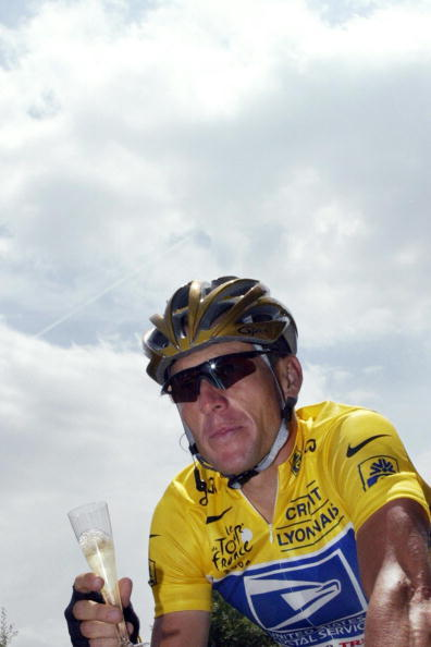 Lance Armstrong holds a glass of champagne during the 20th and last stage of the 91st Tour de France cycling race on July 25, 2004.