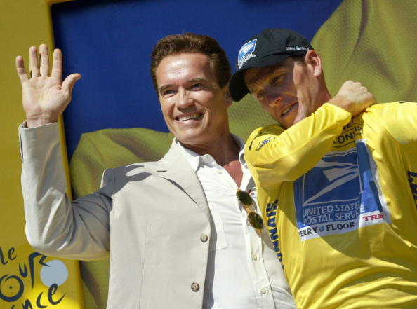 Lance Armstrong and actor Arnold Schwarzenegger celebrate on the podium at the end of the 11th stage of the 90th Tour de France on July 17, 2003.