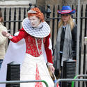 A man dressed as Queen Elizabeth I waits along the processional route.
