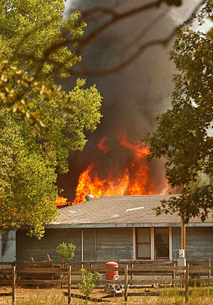 A barn burns behind a home south of Todd Mission, Texas.