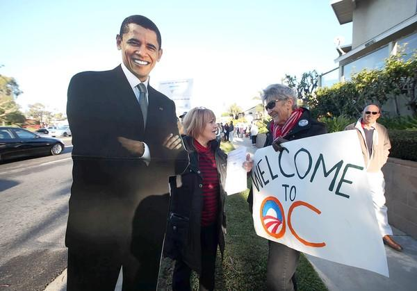 Holding a life-sized cuttout, Ilese Baeck, left, and Beverly Loney, come out to support President Obama's visit to Orange County for a fundraising breakfast as they joined hundreds of others on East Coast Highway and Seaward Road in Corona Del Mar.