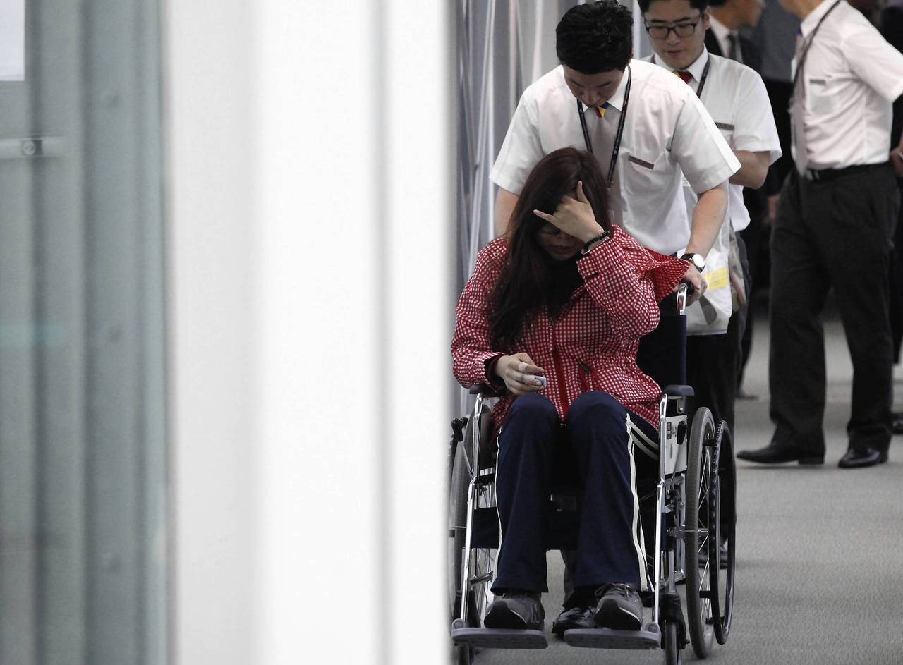 A passenger who was on the crashed Asiana Airline's aircraft, is helped upon her arrival at Incheon Airport in Incheon, South Korea.