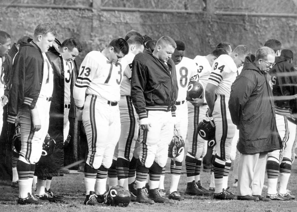 Chicago Bears bench before the beginning of a game against the Pittsburgh Steelers on Nov, 25, 1963. The Bears bow their heads in memory of President John F. Kennedy. From left are: Bennie McRae (26), Bob Kilcullen, Joe Fortunato, Steve Barnett (73), Wetoska, Willie Galimore (28), Joe Marconi (34), and coach Phil Handler.