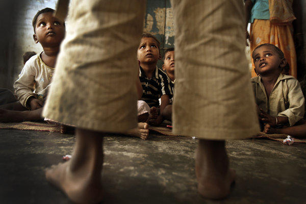 Children listen as they await a midday meal at a community center on the outskirts of Lucknow. (Rick Loomis / Los Angeles Times)