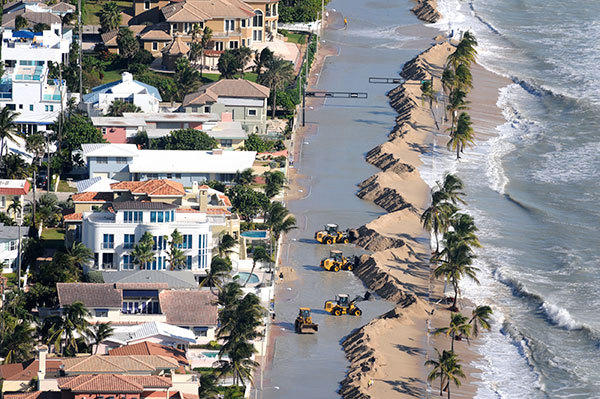 Storm surge related flooding remains along A1A just north of Sunrise Blvd. as work crews continue to push sand off the roadway.