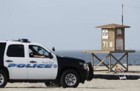 A Newport Beach police vehicle drives by Lifeguard Tower 71, where a dead body was found Monday.