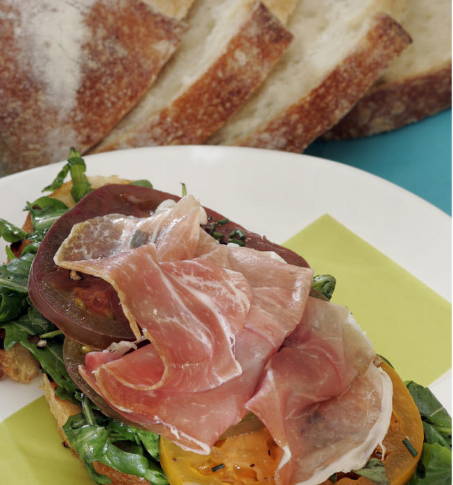 Open-faced arugula, heirloom tomato and prosciutto sandwich