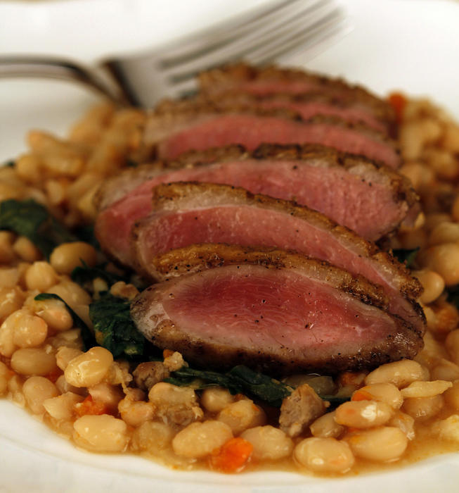 Crisp-skinned duck breasts on white beans with dandelion greens