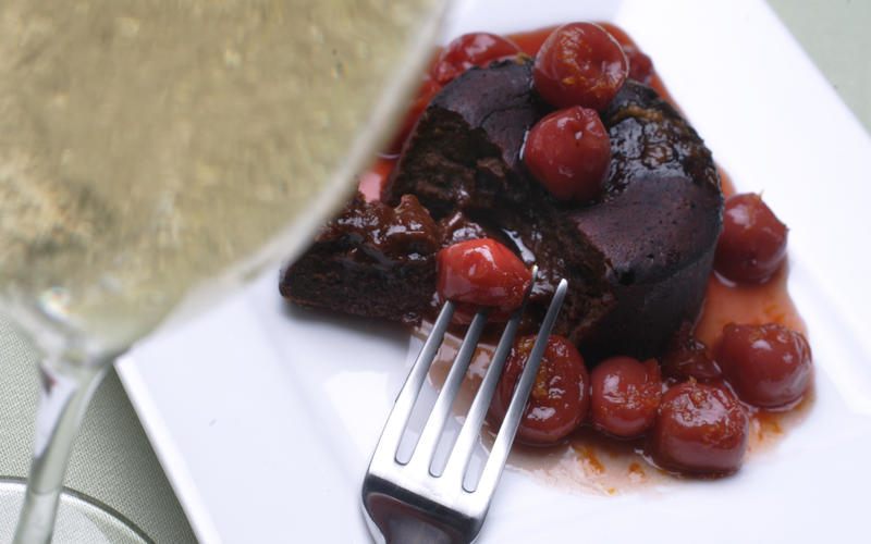 Flaming cherries over individual chocolate cakes
