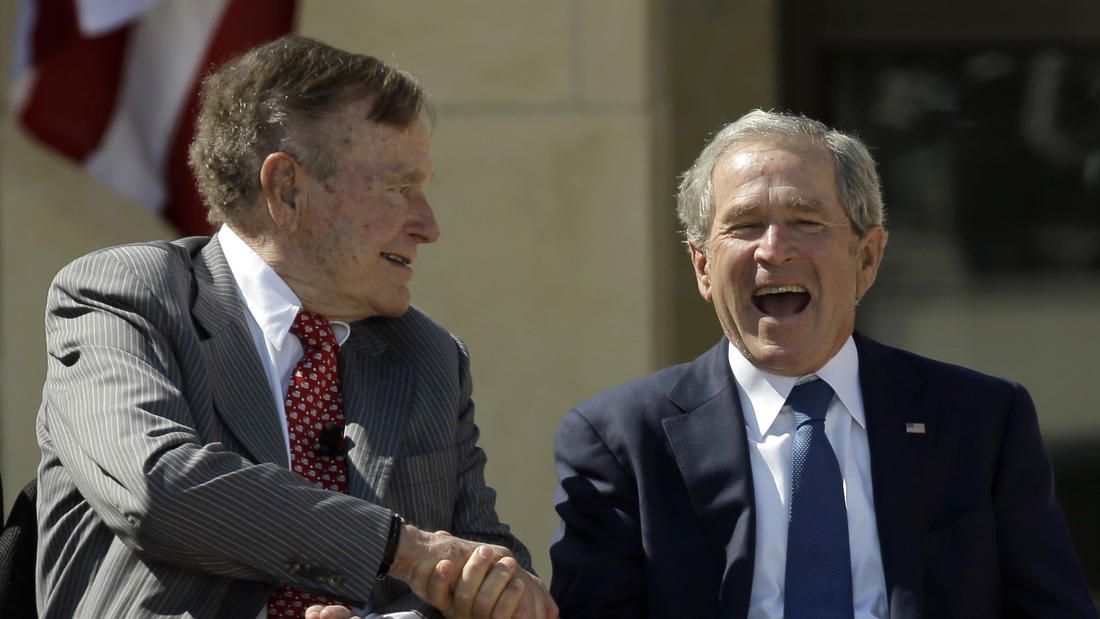 Former President George H.W. Bush shakes hands with his son, former President George W. Bush, during the dedication of the George W. Bush Presidential Center in Dallas.