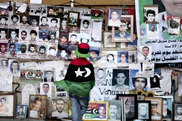 A girl wrapped in a flag looks at pictures of people killed in Libya.