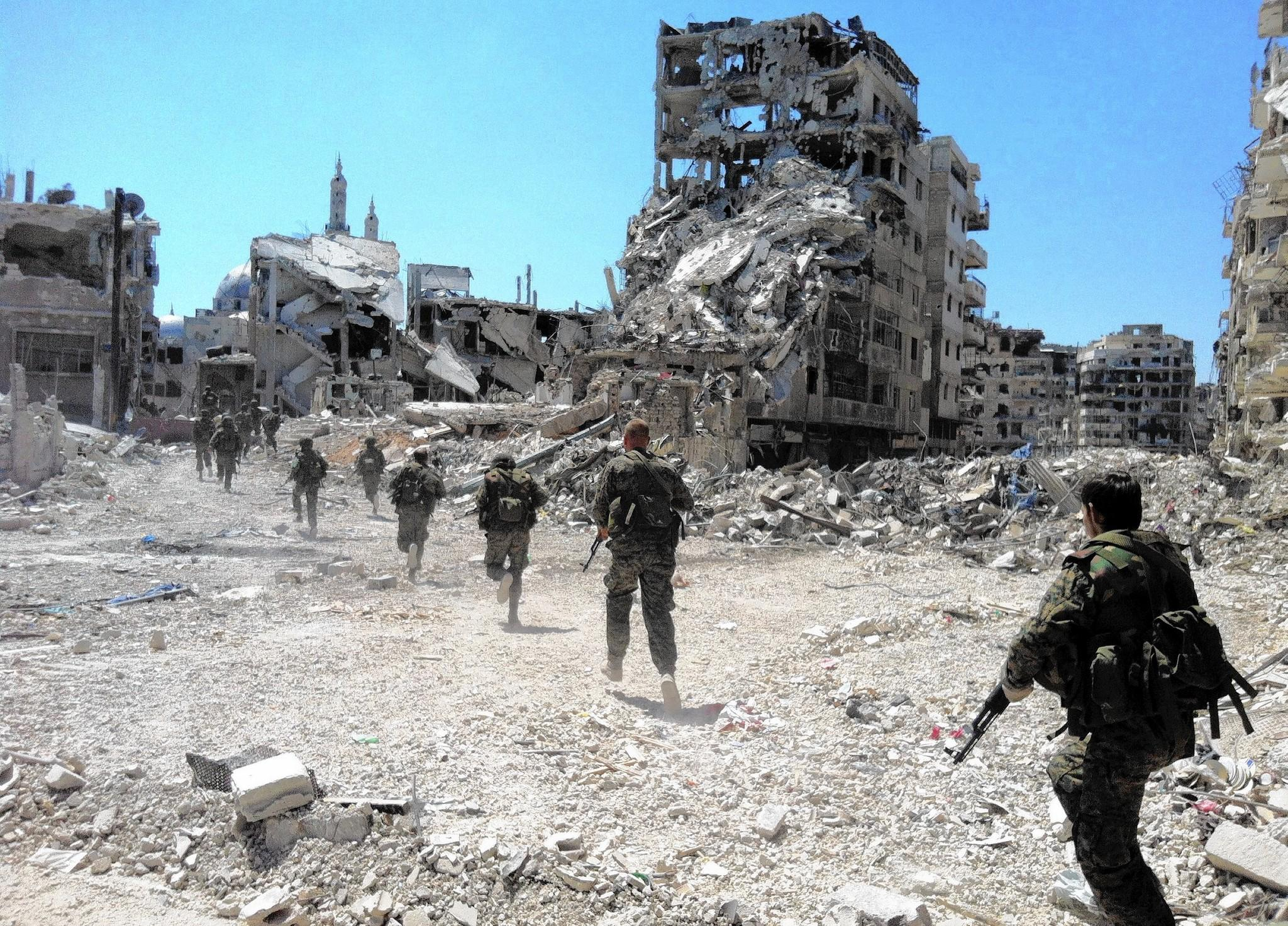 A photo from July 2013 shows Syrian government forces patrolling in the central city of Homs.  (AFP/Getty Images)