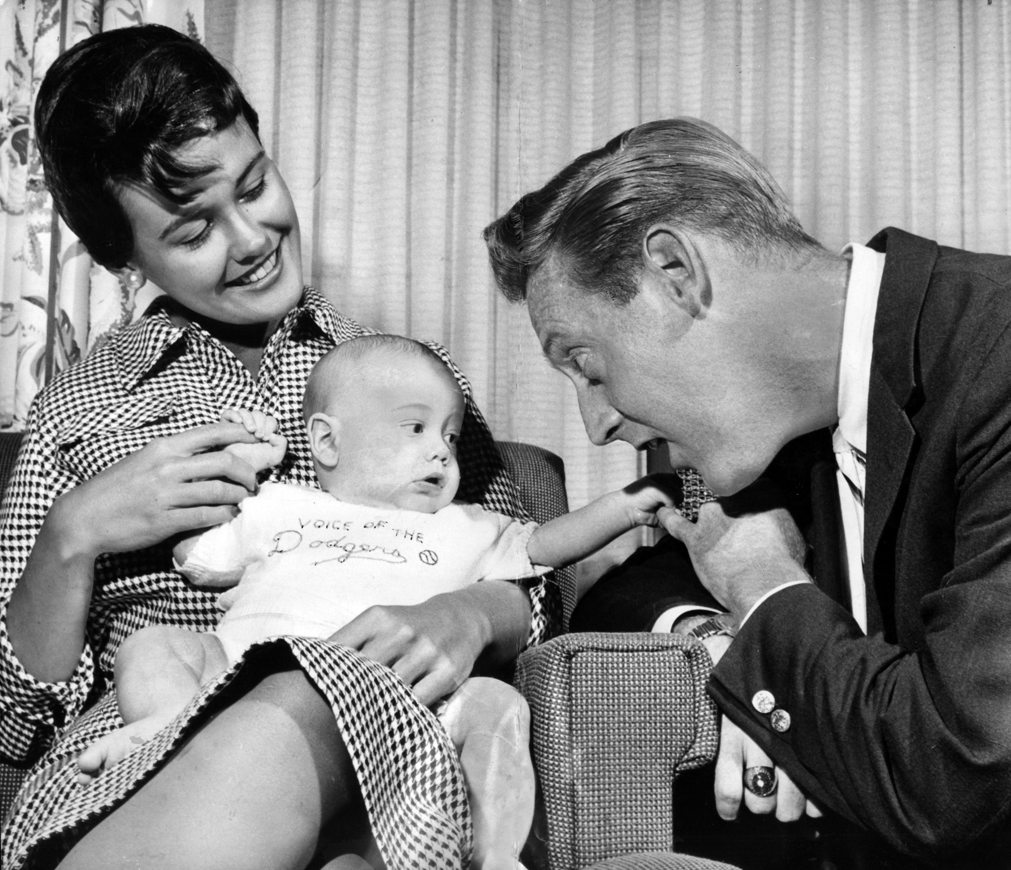 Joan and Vin Scully hold their two-month-old son Michael in April 1960.