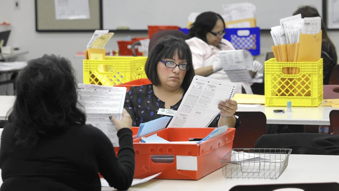 Lydia Harris, a temporary worker at the Sacramento Registrar of Voters, looks over a mail-in ballot before it is sent to be counted a week after polls closed in the 2014 election.