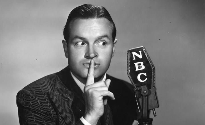 A 1947 photo of Bob Hope holding an NBC-emblazoned microphone.