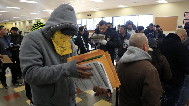 Illegal Alien covers his face while getting a driver's license