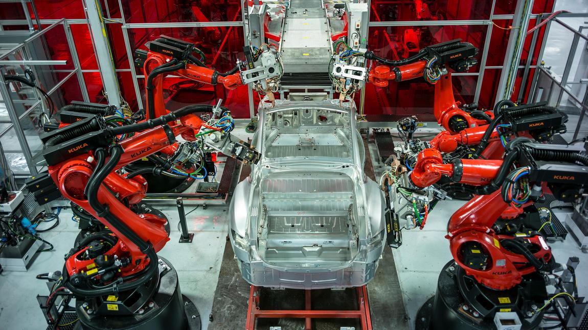 Robots at the Tesla factory putting together a car