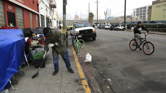 Dozens of California cities have laws targeting the homeless. Above, a skid row resident sweeps the sidewalk where his belongings are gathered. (Los Angeles Times)