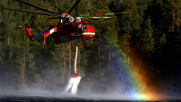 A fire helicopter scoops up water from Jenks Lake as it works to control flames in the Big Bear area. (Rick Loomis / Los Angeles Times)