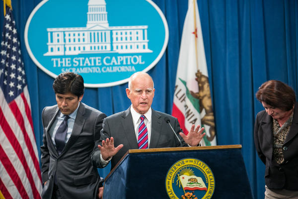 Gov. Jerry Brown, center, talks about gas reduction being dropped from the climate change bill at a Capitol news confrence. (Marcus Yam / Los Angeles Times)