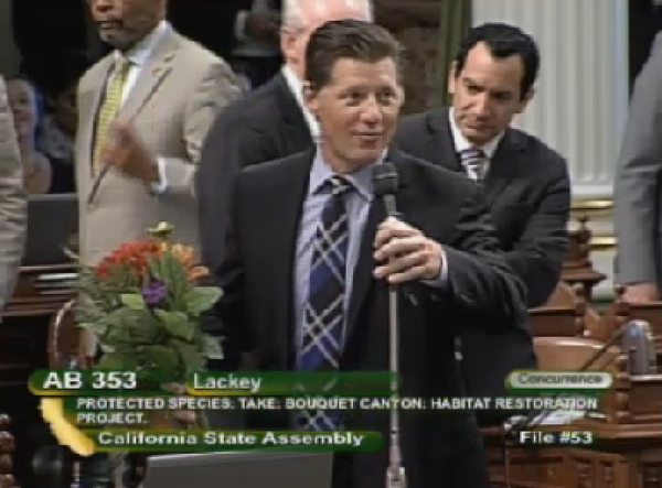 Assemblyman Brian Jones (R-Santee) delivers a bouquet of flowers to fellow lawmaker Tom Lackey (R-Palmdale) on the Assembly floor during debate Thursday. (California Channel)