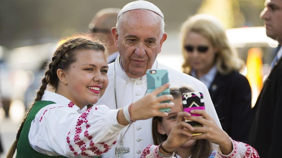Pope Francis has his photo taken with children whose parents work at the Lithuanian Embassy. (Molly Riley / AFP/Getty Images)