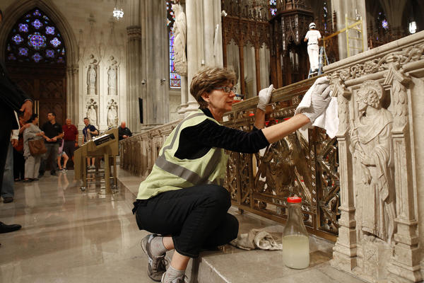 Lucia Popian polishes at St. Patrick's Cathedral in preparation for the pope's visit on Thursday. (Carolyn Cole / Los Angeles Times)