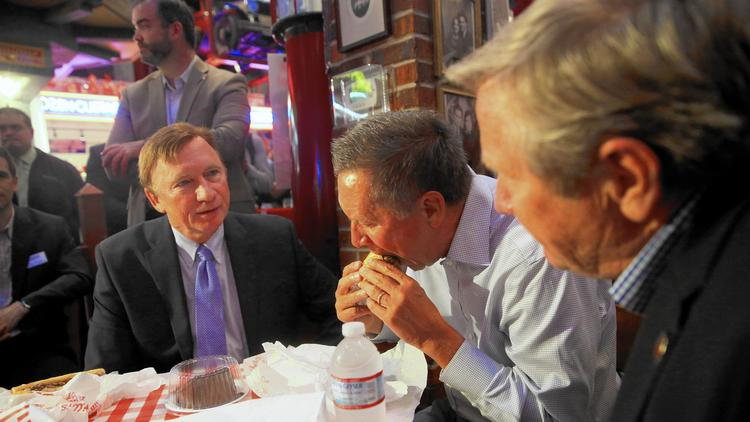 John Kasich eats a hot dog during lunch at Portillo's in River North with restaurant chain Chief Executive Richard J. Portillo, left. (Brian Nguyen / Chicago Tribune) ()