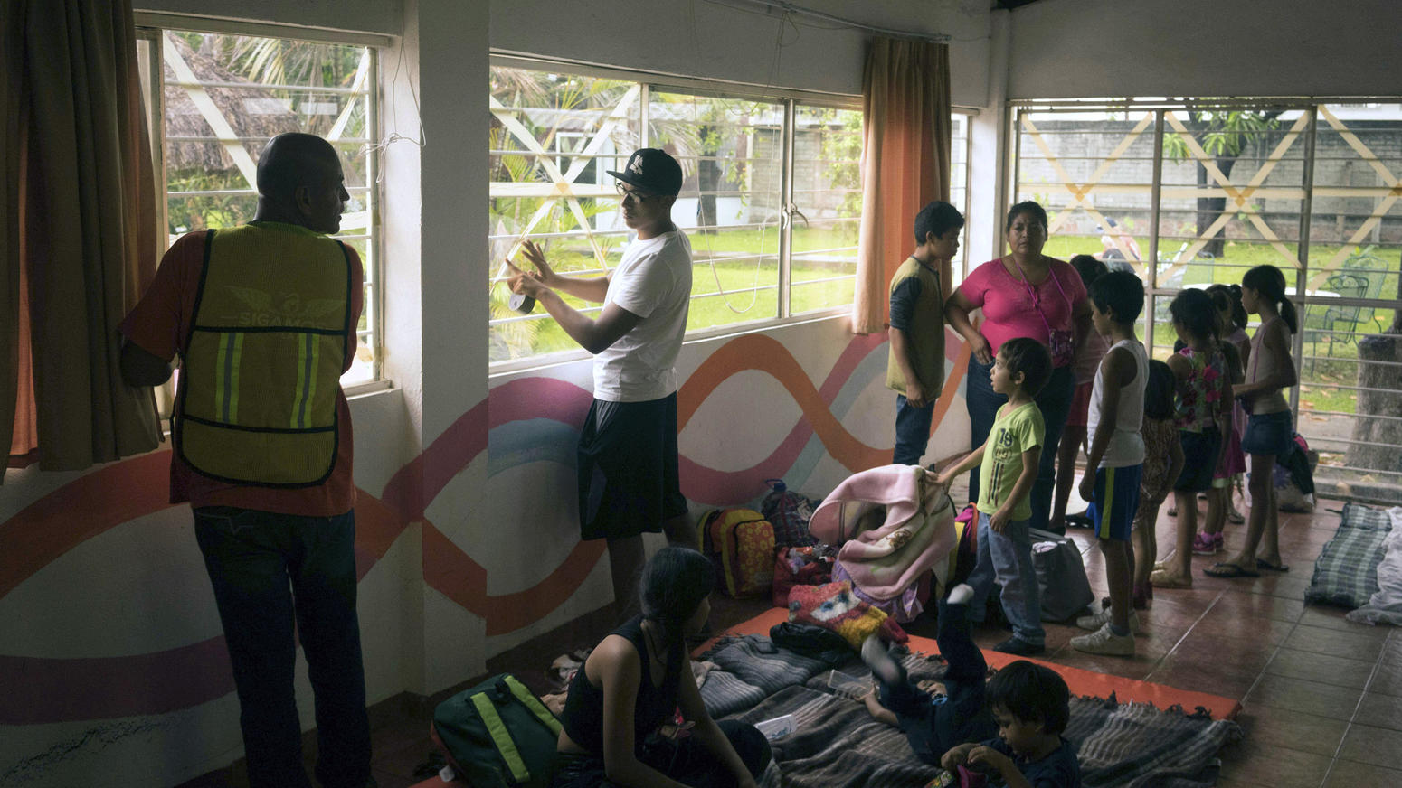 Men tried to secure the windows at a makeshift shelter in Puerto Vallarta. ()