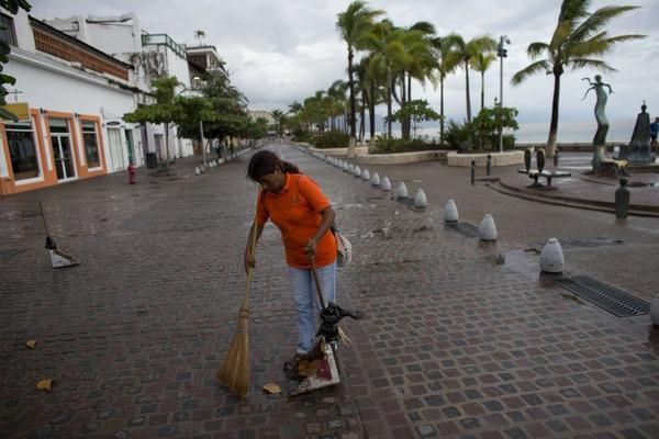 A city cleaner sweeps normal leaves and debris from a seafront walkway, the morning after Hurricane Patricia passed farther south, sparing Puerto Vallarta, Mexico. (Associated Press)