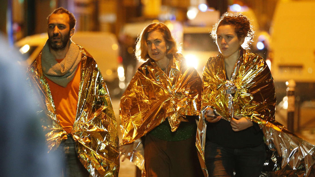 People wrapped in emergency blankets walk near the Bataclan concert hall early Saturday morning. (Francois Guillot /AFP/Getty Images)