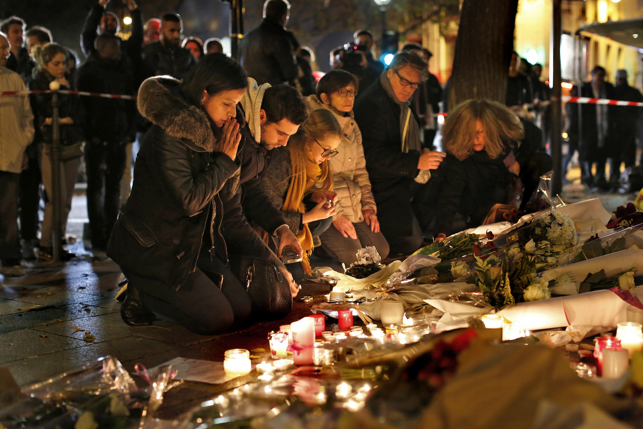 Mourners place flowers and candles outside the Bataclan theater in Paris. (Carolyn Cole / Los Angeles Times)