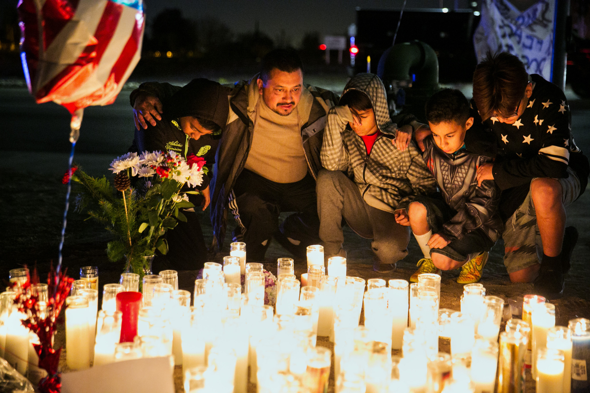 People kneel in prayer for victims in San Bernardino. (Marcus Yam / Los Angeles Times)