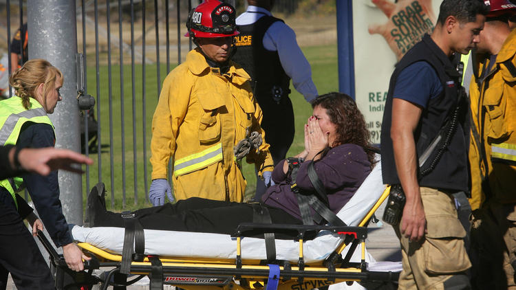 A victim is wheeled away on a stretcher. (David Bauman / The Press-Enterprise)