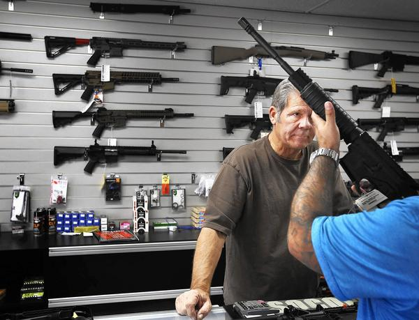 Frank Cobet of Get Loaded in Grand Terrace shows a customer a AR-15 rifle. (Barbara Davidson / Los Angeles Times)