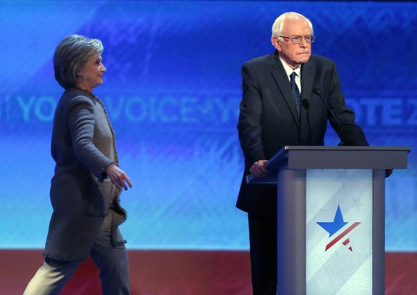 Hillary Clinton returns to the stage after the Democratic presidential primary debate had resumed from a break, as Bernie Sanders stands at his lectern. (Jim Cole / AP)