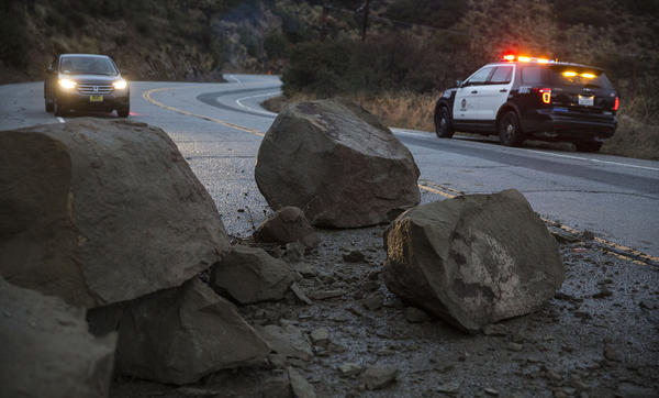 Large boulders block Santa Susanna Pass Road two miles west of Topanga Canyon after a rain-soaked hillside slid onto the roadway in Chatsworth. (Brian van der Brug / Los Angeles Times)