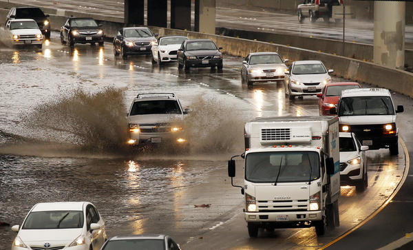 Vehicles navigate the southbound 101 Freeway at California Street in downtown Ventura as lanes are blocked with standing water. (Al Seib / Los Angeles Times)